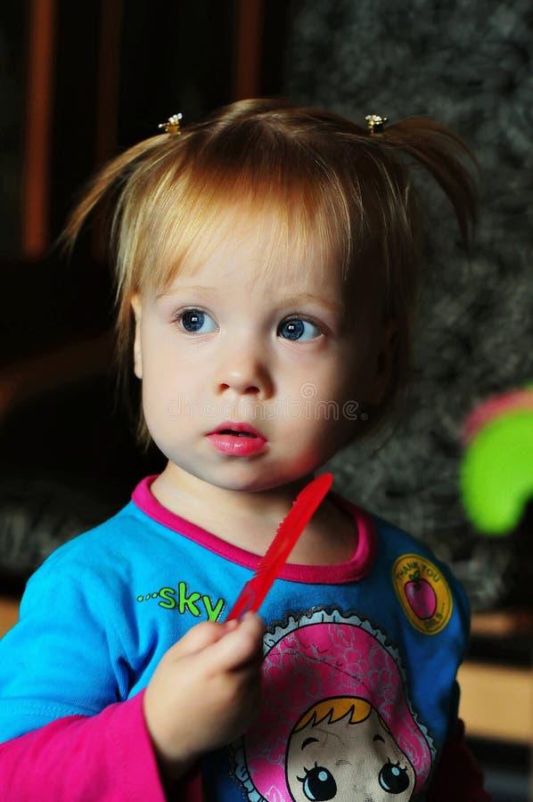 Hållande ögonen på TV för liten härlig flicka hemma royaltyfri fotografi