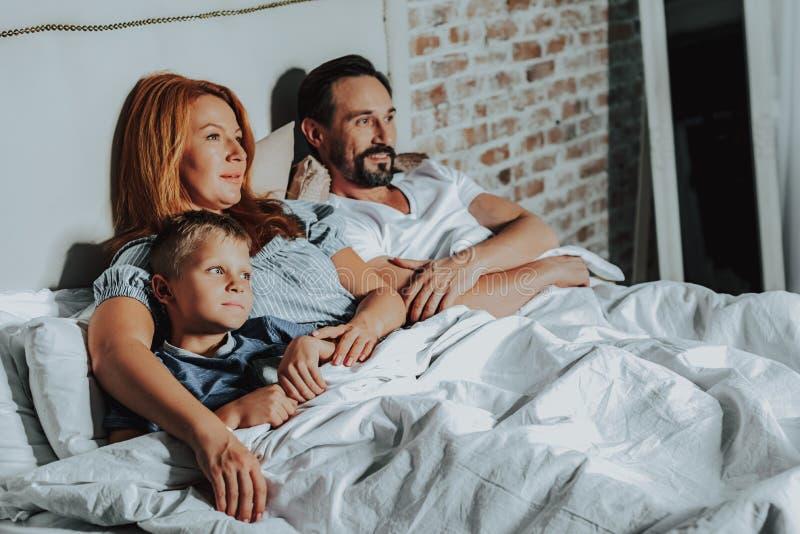 Hållande ögonen på TV för lycklig familj som lägger i säng arkivfoton