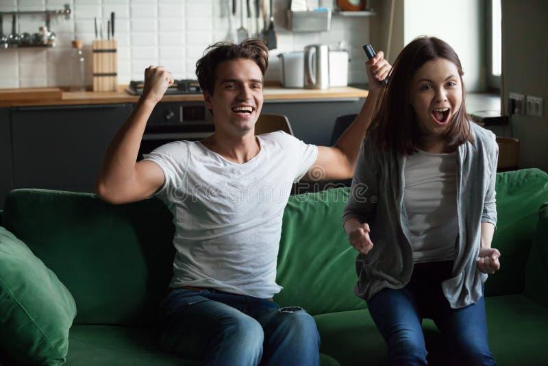 Hållande ögonen på TV för lyckliga barnpar hemma royaltyfria foton