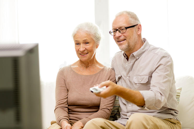 Hållande ögonen på tv för lyckliga höga par hemma arkivbilder