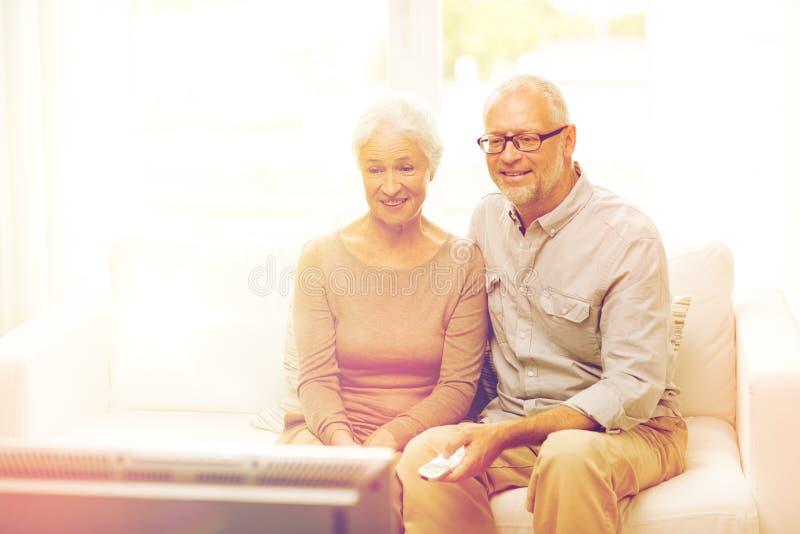 Hållande ögonen på tv för lyckliga höga par hemma royaltyfri bild