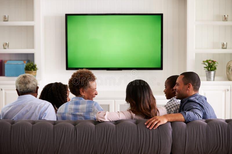 Hållande ögonen på TV för mång- utvecklingsfamilj och skratta, tillbaka sikt royaltyfri foto