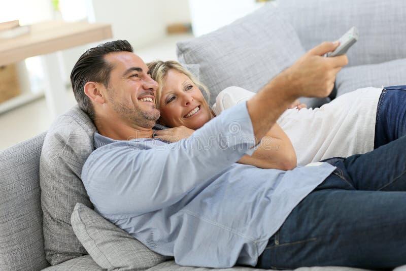 Hållande ögonen på tv för medelåldersa par på soffan royaltyfri fotografi