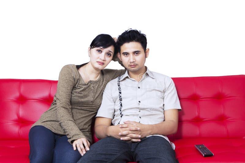 Hållande ögonen på TV för olyckliga par och sitta på den röda soffan fotografering för bildbyråer