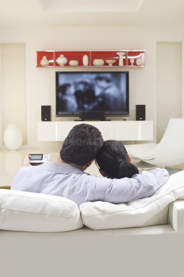 Hållande ögonen på TV för par royaltyfri bild