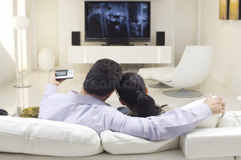Hållande ögonen på TV för par arkivfoton