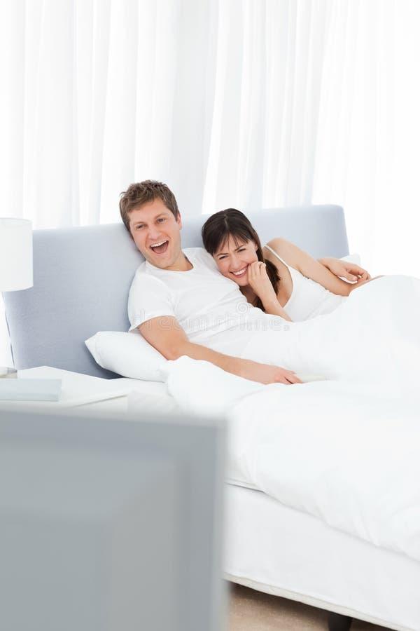 Hållande ögonen på tv för par i deras underlag royaltyfri fotografi
