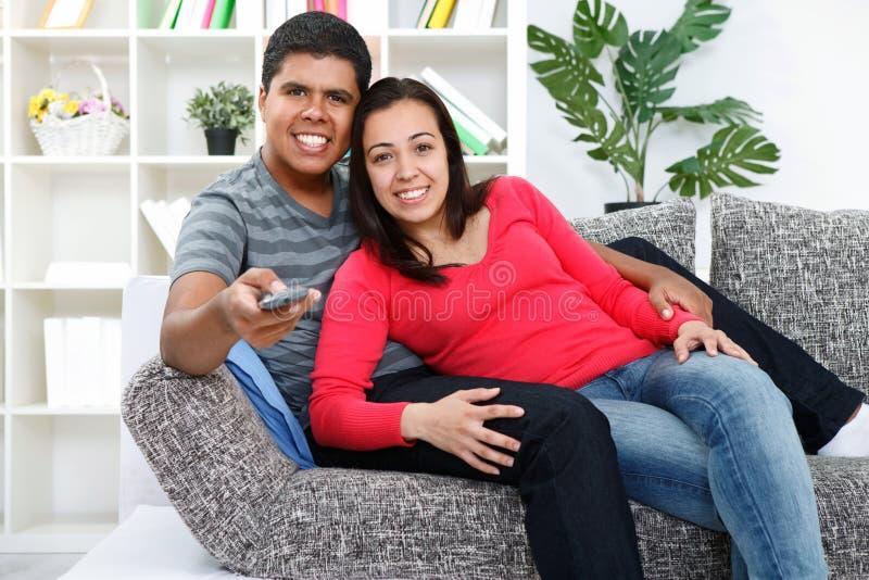 Hållande ögonen på TV för par i deras vardagsrum royaltyfri foto