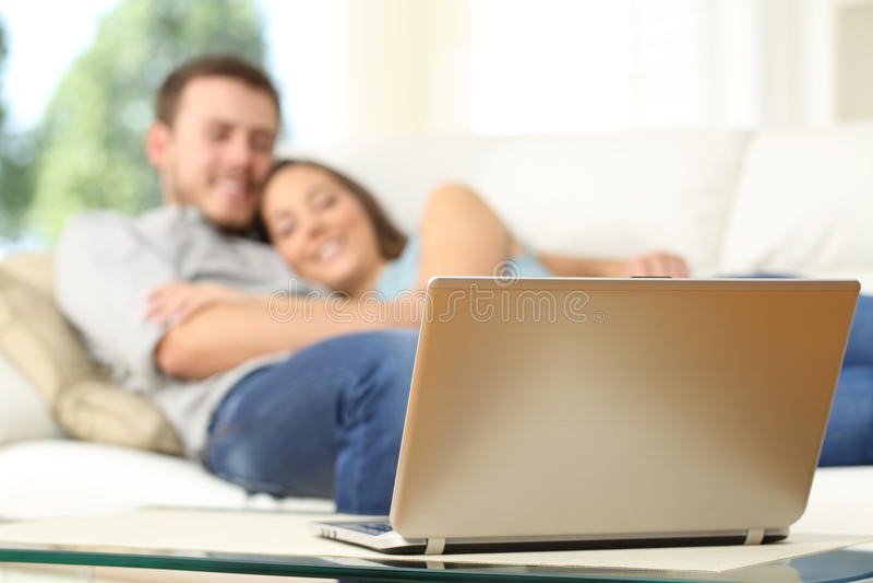 Hållande ögonen på tv för par i en bärbar dator fotografering för bildbyråer