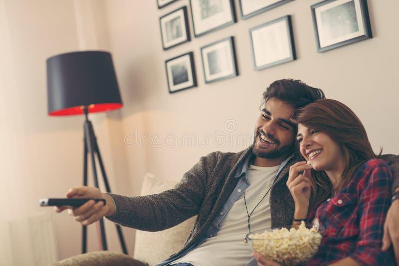 Hållande ögonen på tv för par och ätapopcorn arkivbild