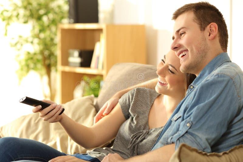 Hållande ögonen på tv för par på en soffa hemma royaltyfri fotografi