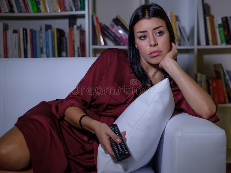 Hållande ögonen på tv för trött uttråkad kvinna i aftonen royaltyfri bild