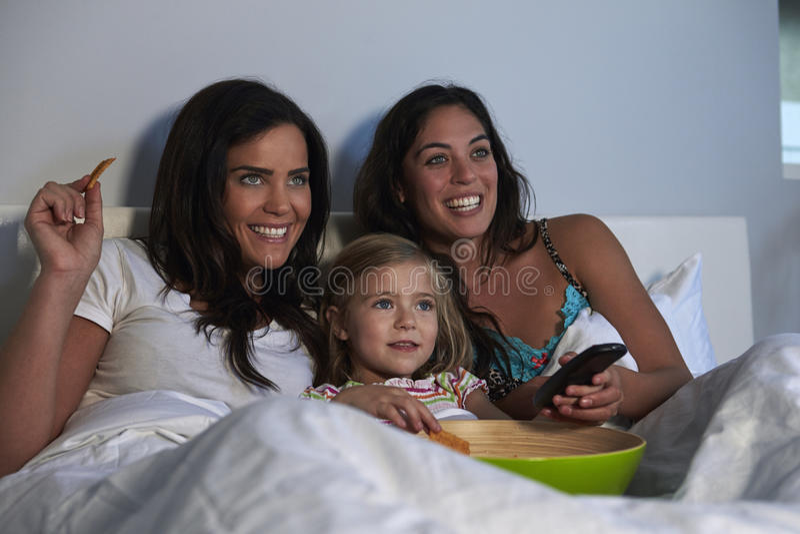 Hållande ögonen på TV för ung flicka i säng med glade kvinnliga föräldrar arkivfoton