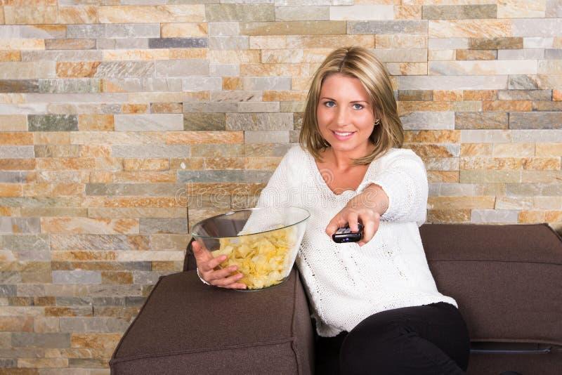 Hållande ögonen på tv för ung kvinna hemma arkivfoton