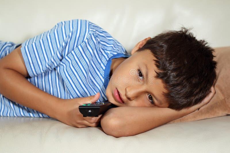 Hållande ögonen på TV för ung pojke arkivfoto