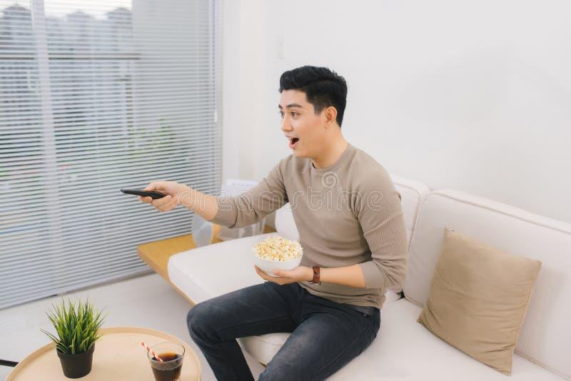 Hållande ögonen på TV för ung stilig man på soffan hemma arkivfoto