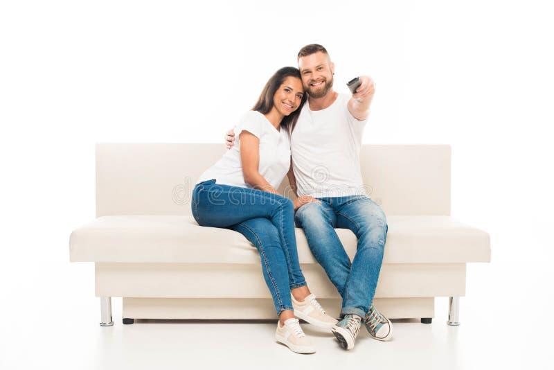 hållande ögonen på tv för unga attraktiva par och användafjärrkontroll, royaltyfria foton