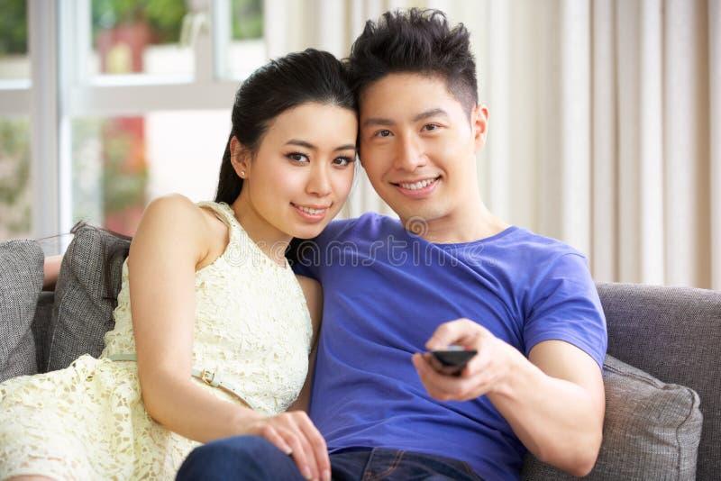 Hållande ögonen på TV för unga kinesiska par på sofaen hemma royaltyfri foto