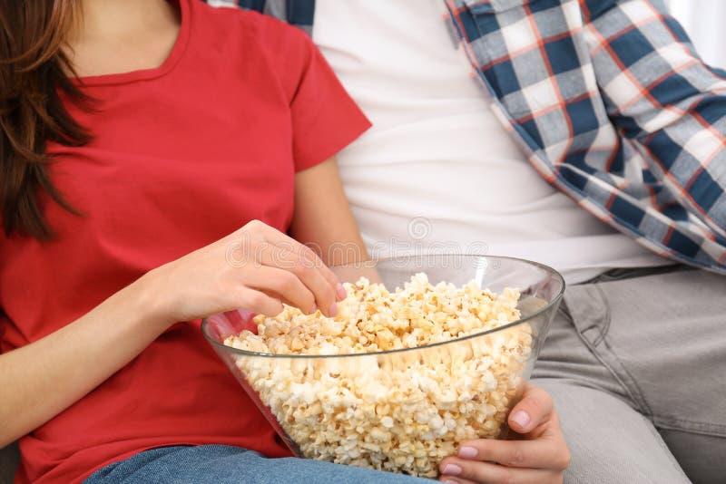 Hållande ögonen på TV för unga par med popcorn på soffan arkivbild