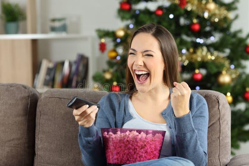 Hållande ögonen på tv för upphetsad kvinna på jul royaltyfri foto