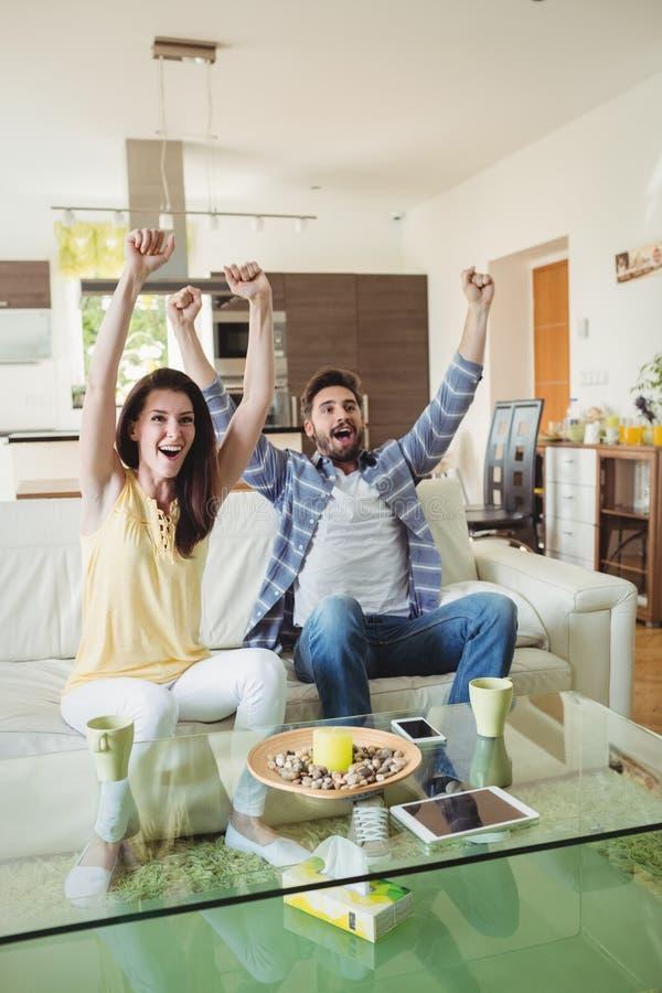 Hållande ögonen på tv för upphetsade par tillsammans arkivbild