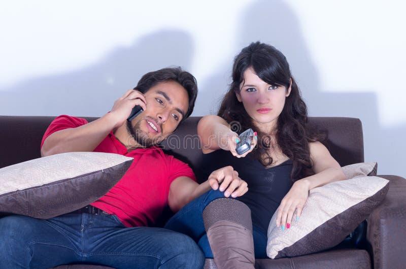 Hållande ögonen på tv för uttråkad flickvän, medan pojkvännen pratar arkivbilder