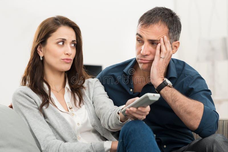 Hållande ögonen på tv för uttråkade par royaltyfri bild