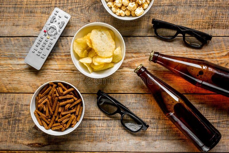 hållande ögonen på TV med chiper, öl och fjärrkontroll på bästa sikt för träbakgrund royaltyfria bilder