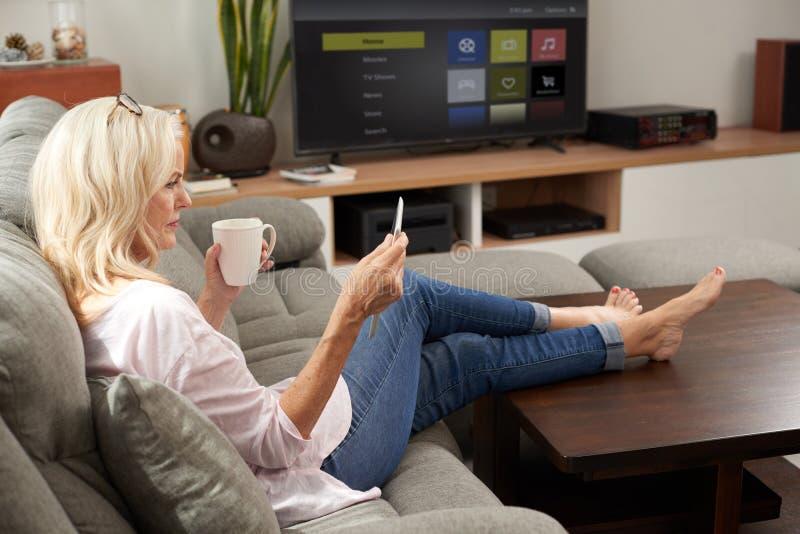 Hållande ögonen på TV-program för hög kvinna hemma royaltyfri fotografi