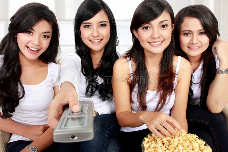 Hållande ögonen på tv samman med vänner arkivfoton