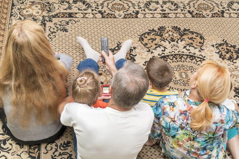Hållande ögonen på tv som sitter på golvet royaltyfri fotografi