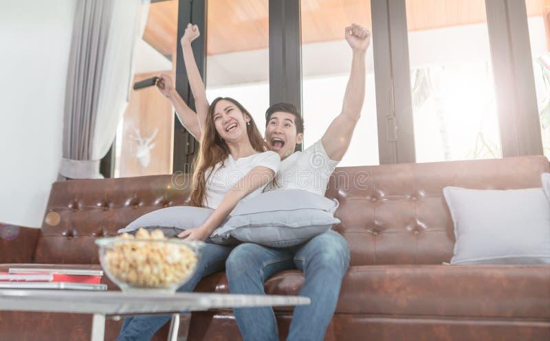 Hållande ögonen på TVsammanträde för asiatiska par på en soffa hemma arkivfoto