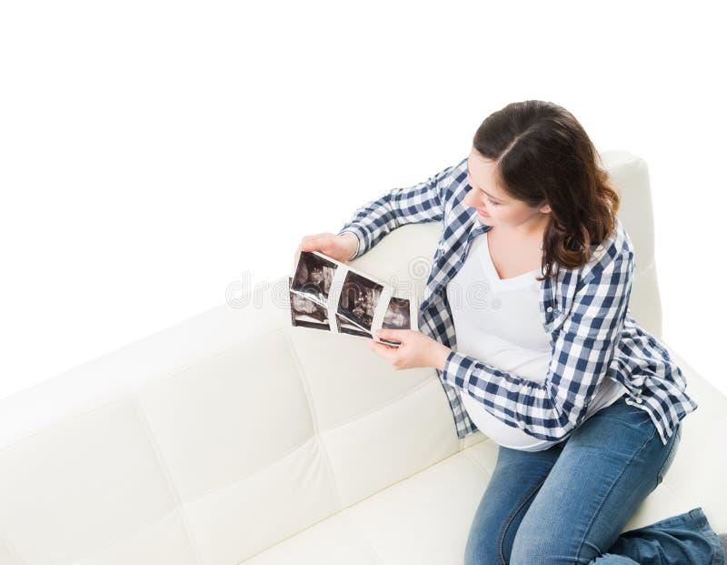 Hållande ögonen på ultraljudsundersökningar för ung härlig lycklig gravid kvinna royaltyfri fotografi