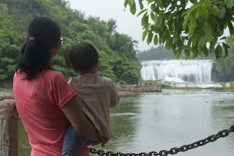 Hållande ögonen på vattenfall för kinesisk mammaomfamningdotter arkivfoto