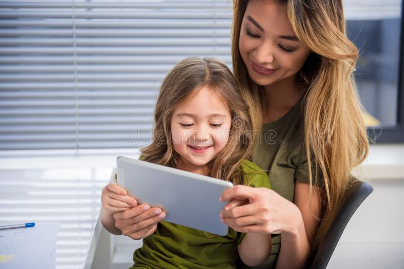 Hållande ögonen på video för gladlynt familj på den digitala grejen royaltyfri fotografi