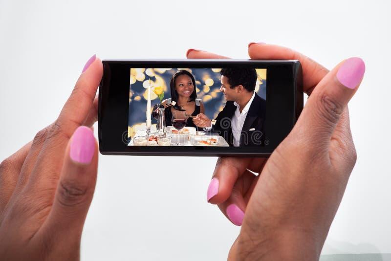 Hållande ögonen på video för kvinna på mobiltelefonen hemma fotografering för bildbyråer