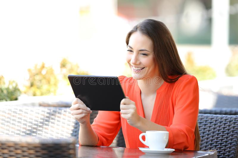 Hållande ögonen på video för lycklig kvinna på minnestavlan i en coffee shop royaltyfria bilder
