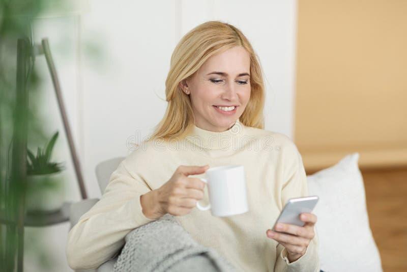 H?llande ?gonen p? video f?r mogen kvinna p? telefonen som dricker te arkivfoton