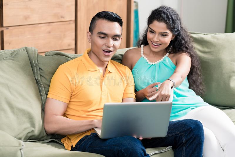 Hållande ögonen på video för par på bärbara datorn arkivfoton