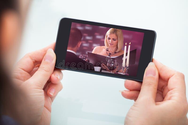 Hållande ögonen på video för person på mobiltelefonen arkivbilder