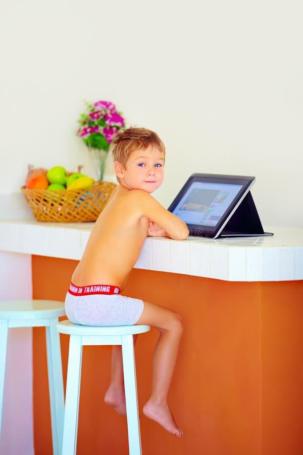 Hållande ögonen på video för ung pys till och med internet, medan sitta i kök i morgonen royaltyfri fotografi