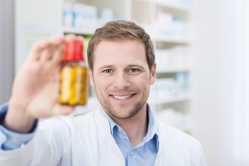 Hållande övre för apotekare en flaska av minnestavlor royaltyfria bilder