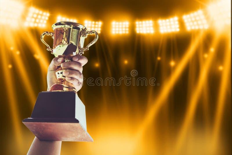 Hållande övre för man en guld- trofékopp, segerbegrepp royaltyfri foto