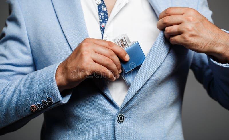 Hållande övre flaska för man av doft Män parfymerar i handen på dräktbakgrund Stilig man i formell dräkt och med arkivfoto
