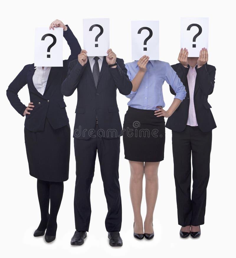 Hållande övre papper för fyra affärspersoner med frågefläcken, fördunklad framsida, studioskott arkivfoton