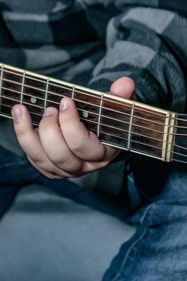 Hållande ackord för hand på gitarren royaltyfri fotografi