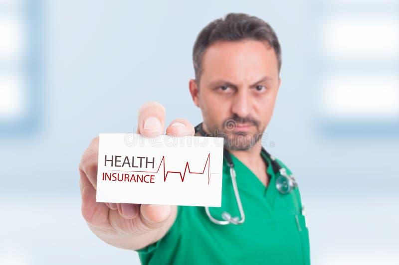Hållande affärs- eller besökkort för allvarlig läkare arkivfoto