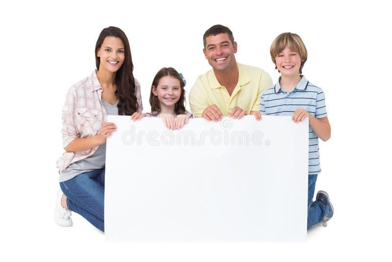 Hållande affischtavla för lycklig familj över vit bakgrund royaltyfri fotografi