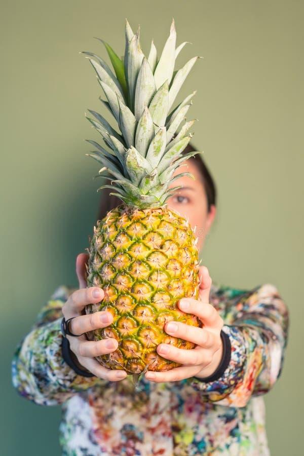 Hållande ananas för modeflicka som är främst av framsida arkivbild