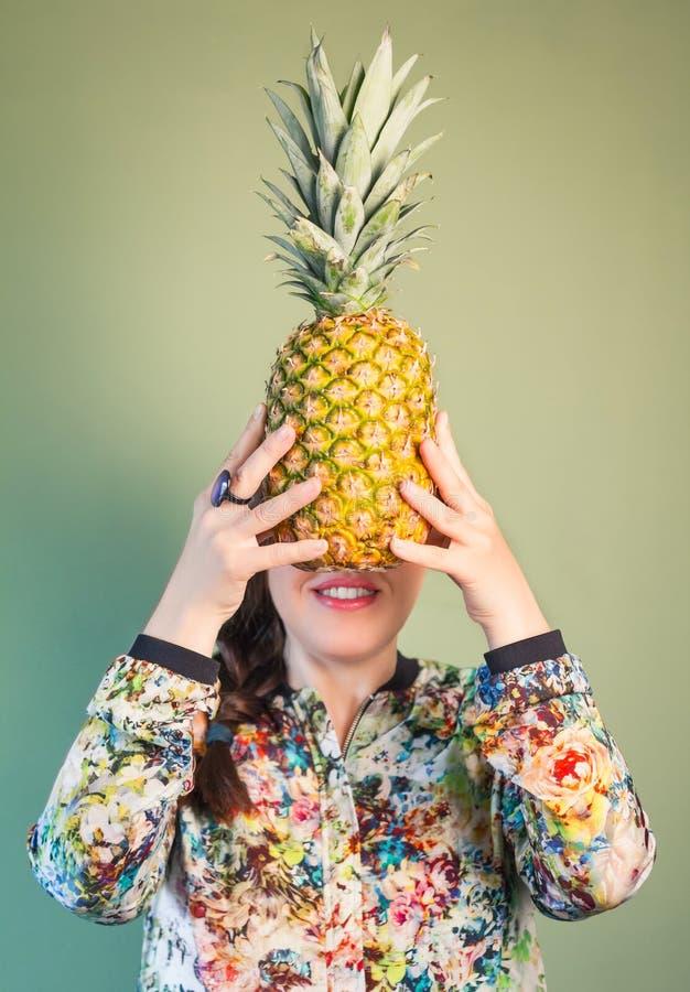 Hållande ananas för modeflicka som är främst av framsida royaltyfria foton